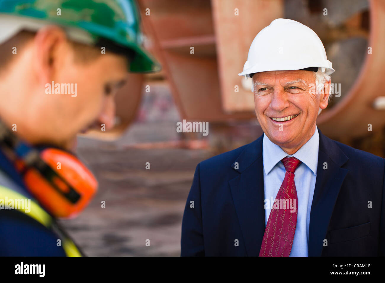 Businessman smiling on dry dock - Stock Image