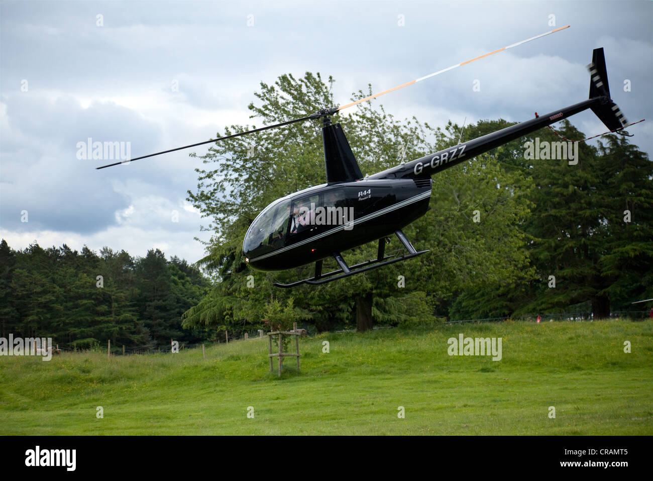 A R44 Raven 91 aircraft G-GRZZ. Robinson Helicopter taking off from Cholmondeley Pageant of Power 2012, Cheshire, - Stock Image