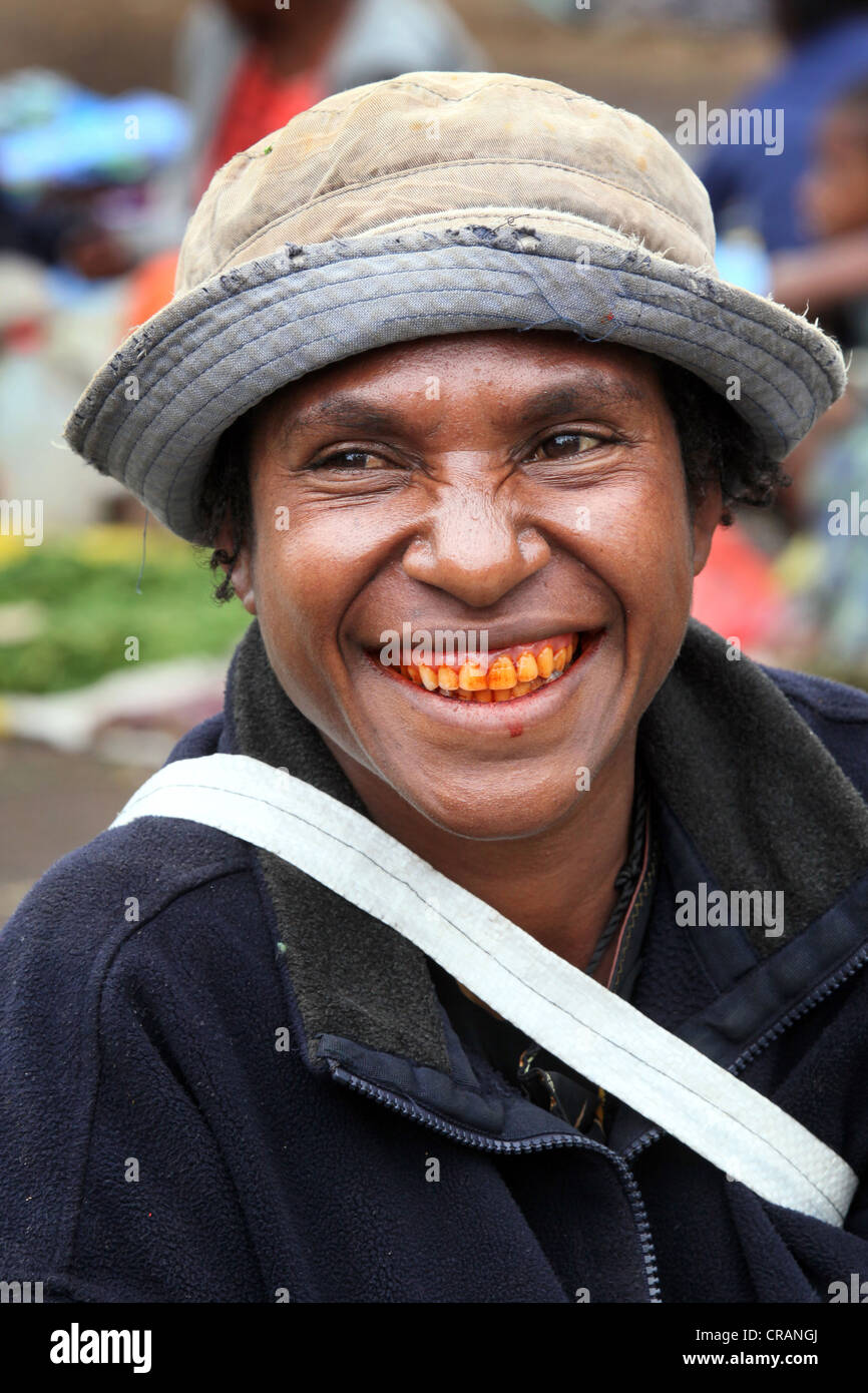 Woman with red teeth from chewing the betel nut at the market of Goroka, Papua New Guinea - Stock Image