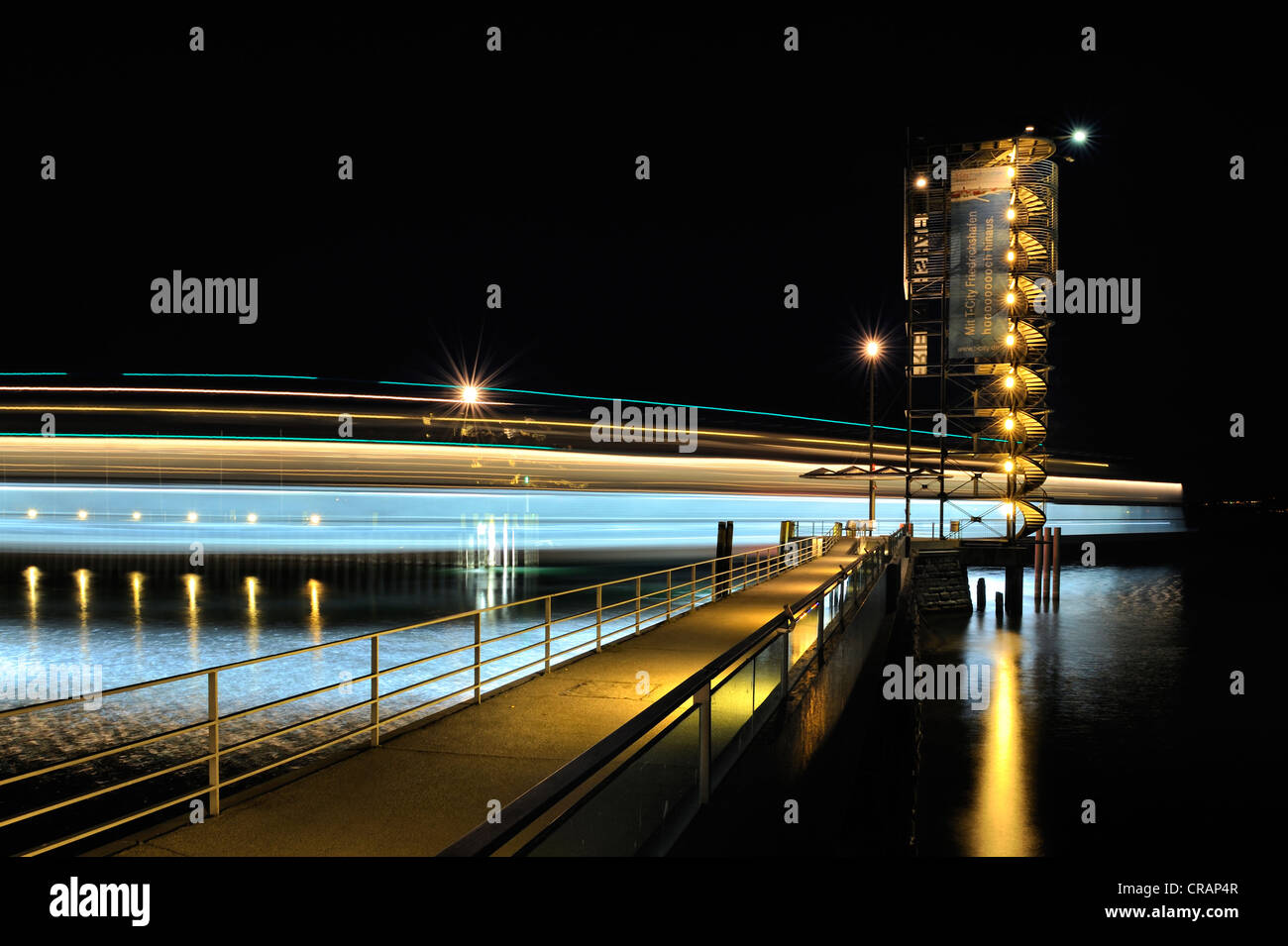Light trace of the moving Euregia ferry and the illuminated Molenturm tower in the ferry port of Friedrichshafen - Stock Image