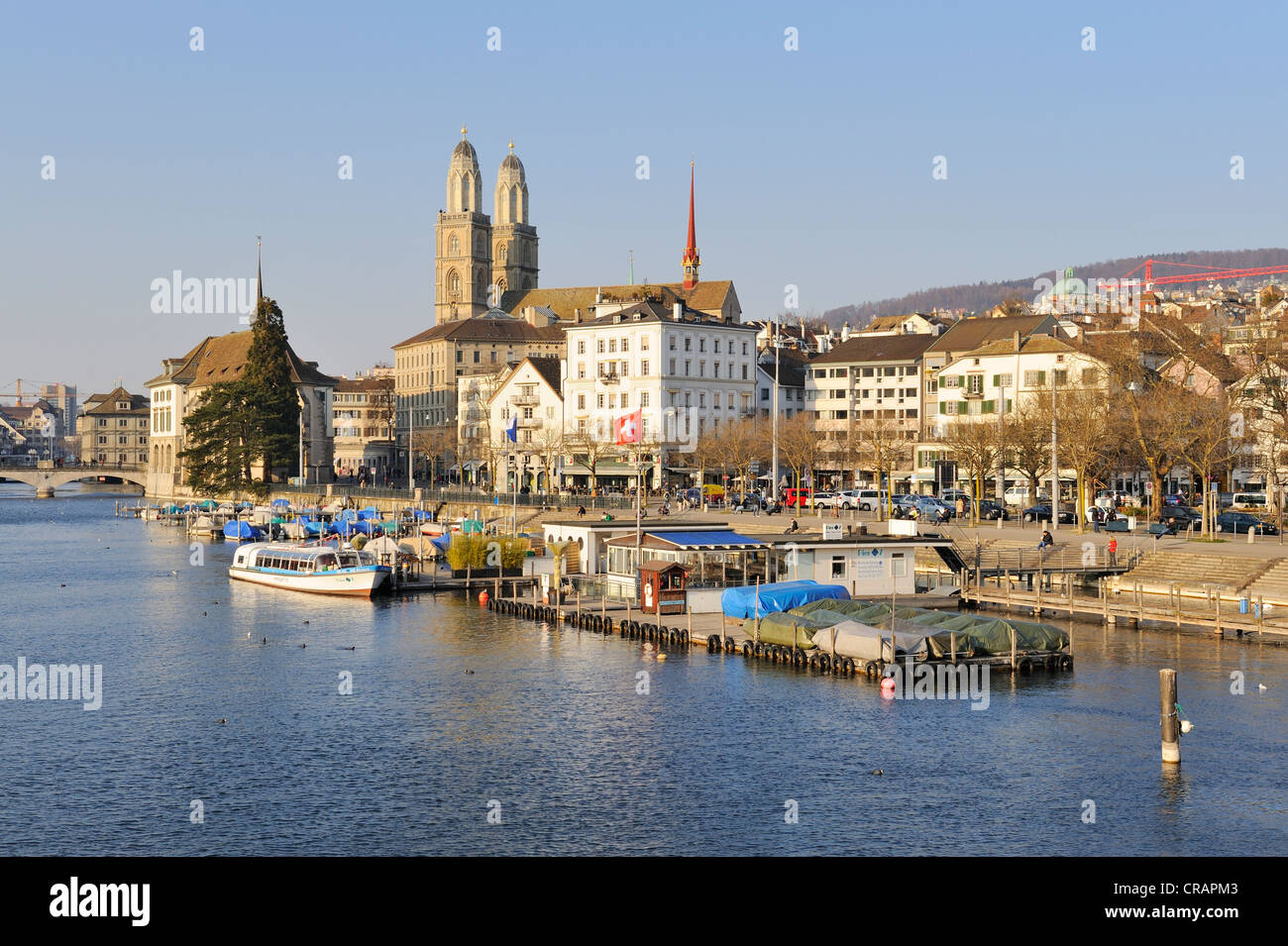 View from the Quai bridge over the Limmat river to the Limmatquai quay with the Grossmuenster great minster, Zurich - Stock Image