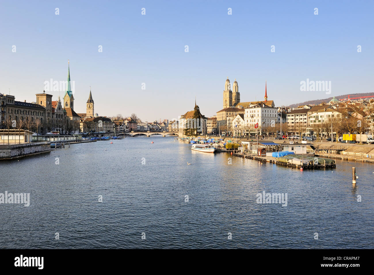 View from the Quai bridge over the River Limmat on the Limmatquai quay and the three city churches, Grossmuenster Stock Photo