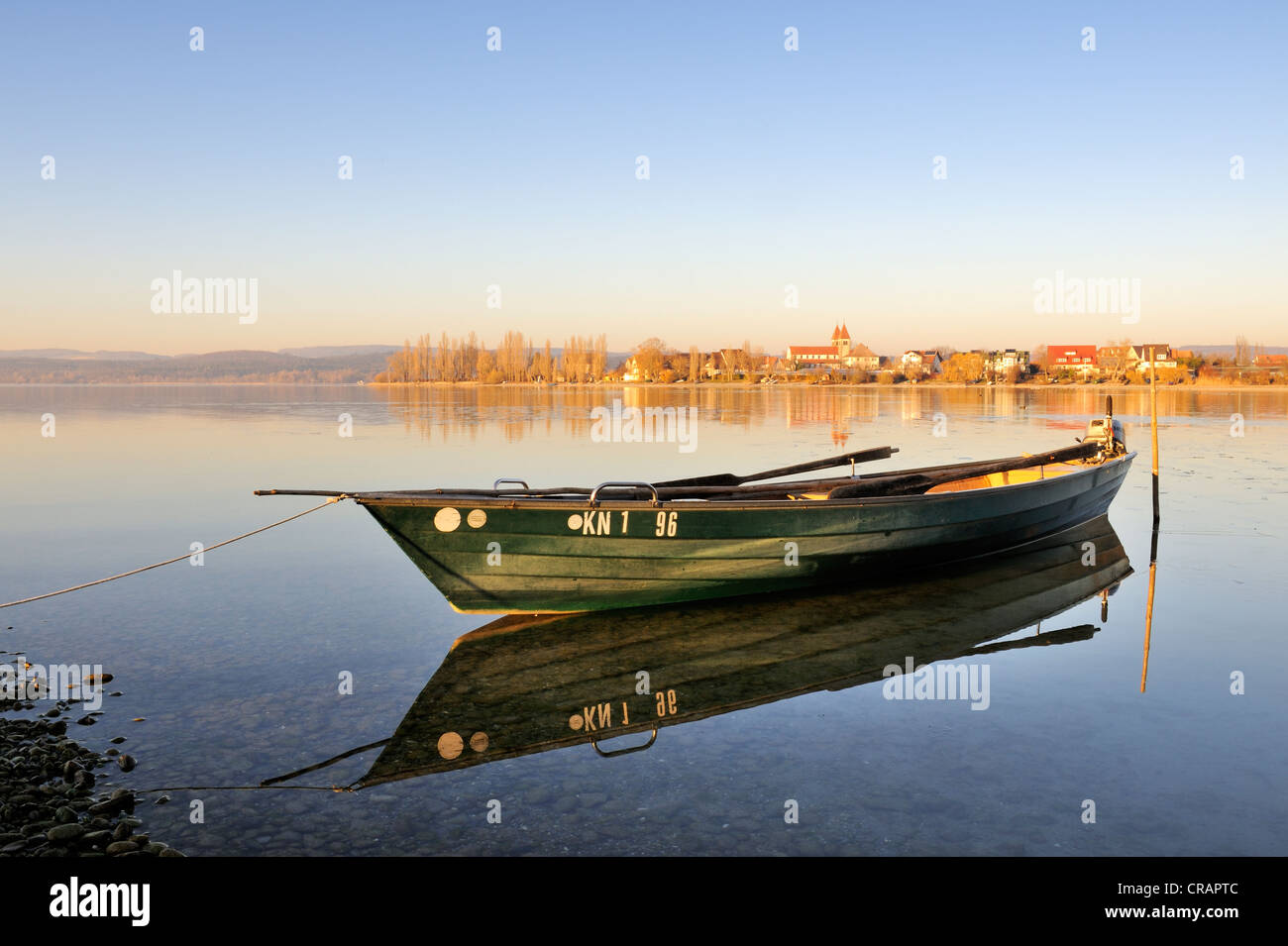 Evening mood with a fishing boat on the shore of the island of Reichenau, at the rear, the Church of St. Peter and - Stock Image