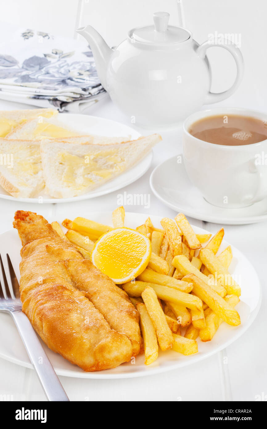 Fish and chips served with buttered bread and a pot of tea. Favourite British seaside supper. - Stock Image