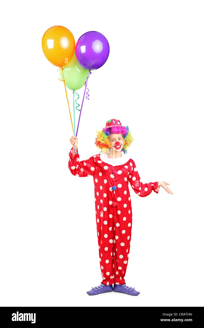 Full length portrait of a female clown, happy joyful expression on face, with a bunch of balloons isolated on white - Stock Image