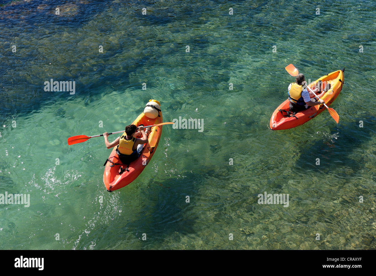 father and son kayaking in the clear waters of cala santa galdana menorca spain balearic islands - Stock Image