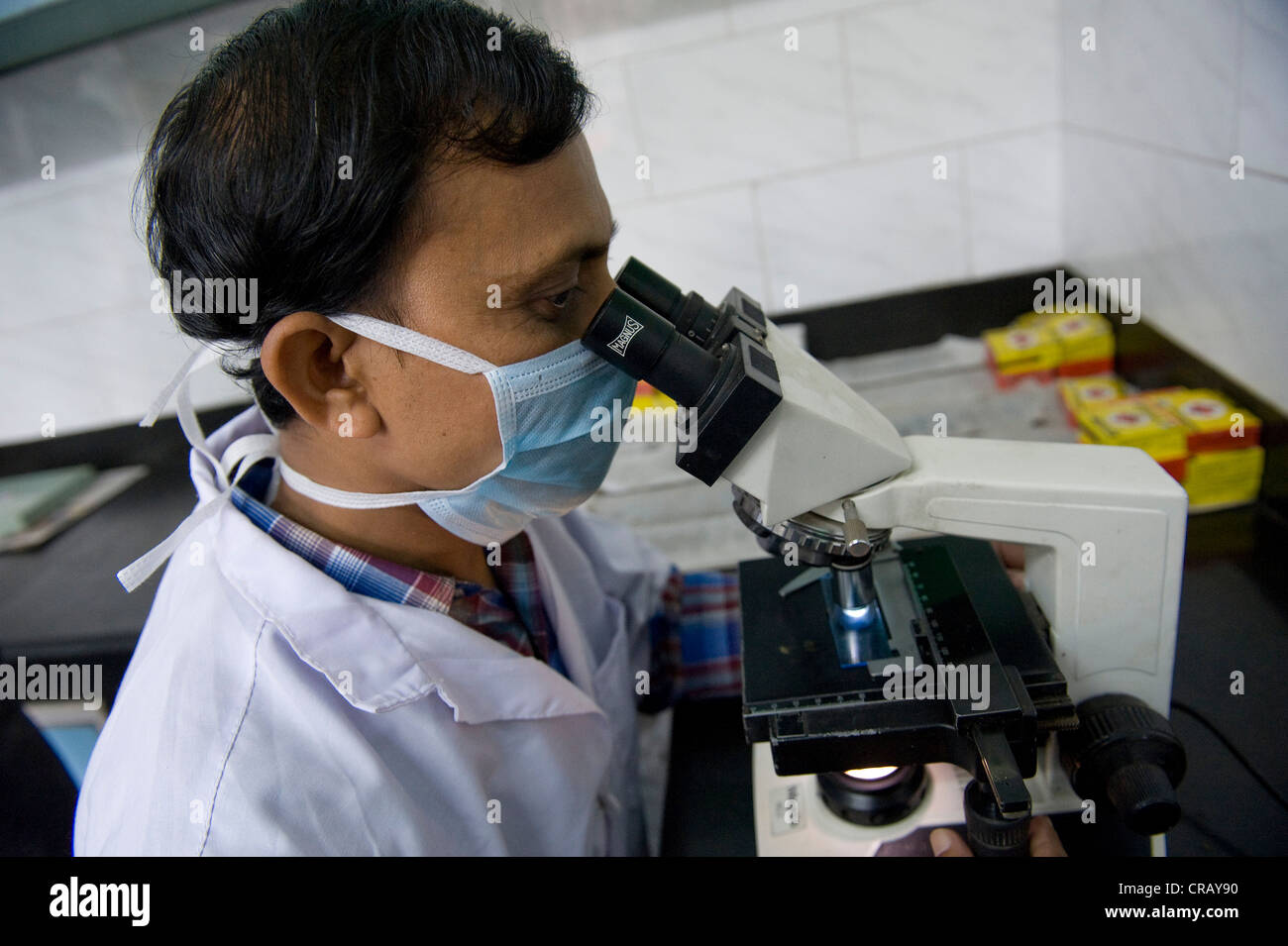 Employee examining a sputum specimen for tuberculosis pathogen under a microscope, St. Thomas Home, Shibpur district, - Stock Image