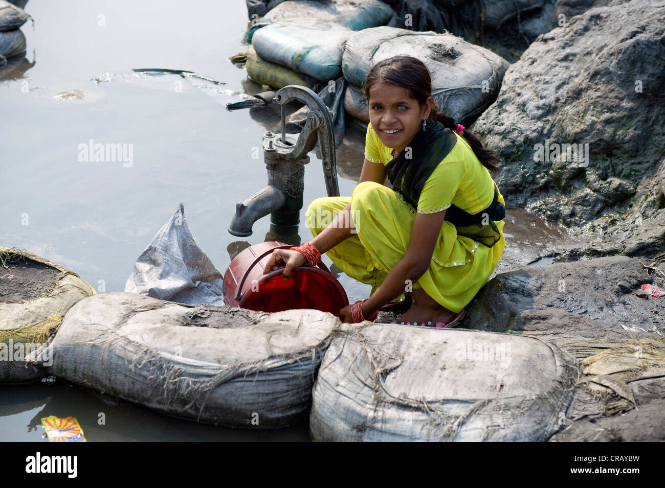 Young woman fetching water from a contaminated pond, Shibpur district, Howrah, Kolkata, West Bengal, India, Asia - Stock Image