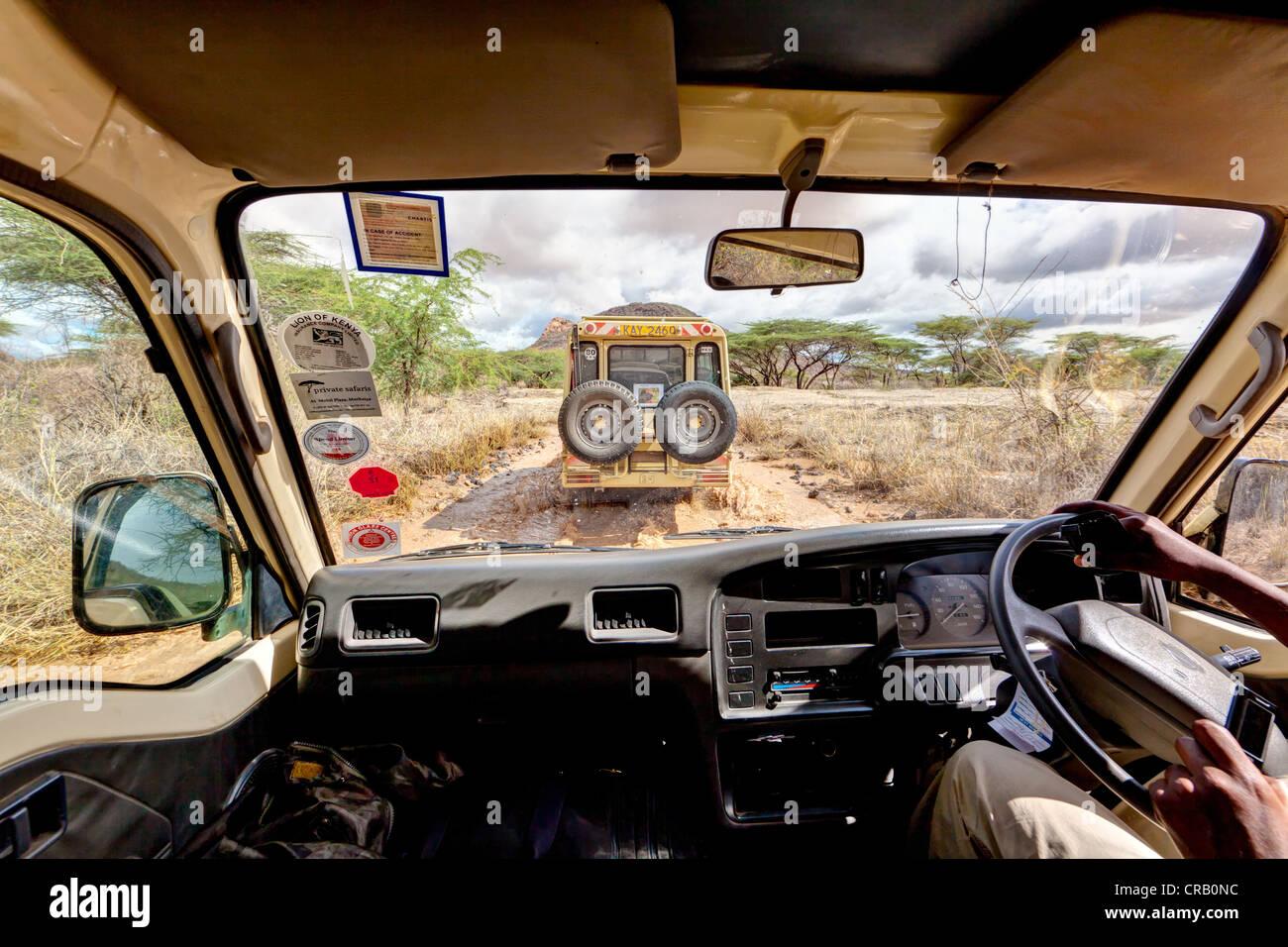 Safari bus following a Landrover over wet dirt tracks in the Samburu National Reserve, Kenya, East Africa, Africa, - Stock Image