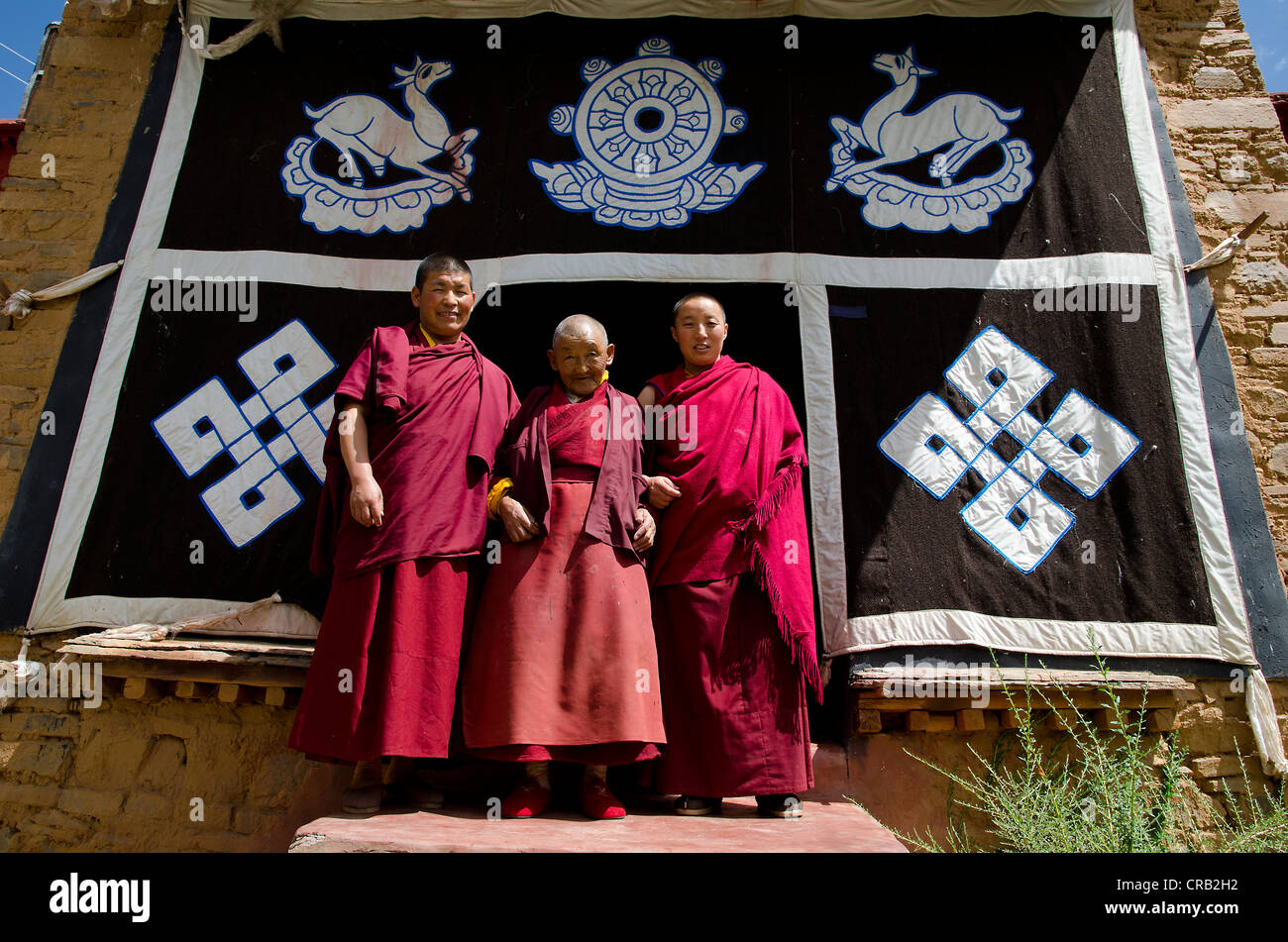 Three Tibetan Buddhist nuns, a younger, a middle-aged and a 70-year-old woman in red monks' robes in front of - Stock Image