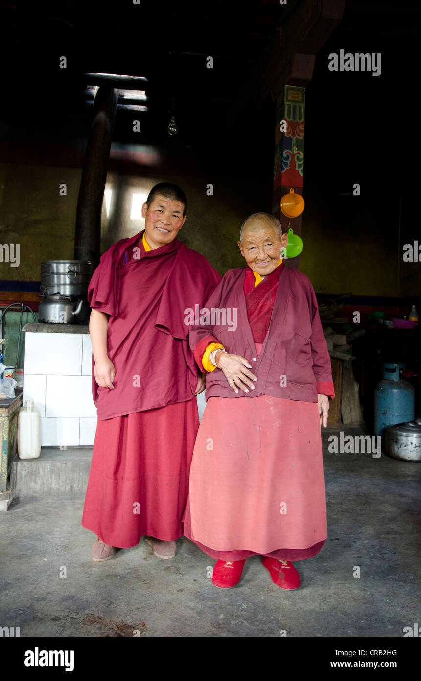 Two Tibetan Buddhist nuns, a younger and a 70-year-old woman in red monks' robes in a monastery kitchen, Gongkar - Stock Image