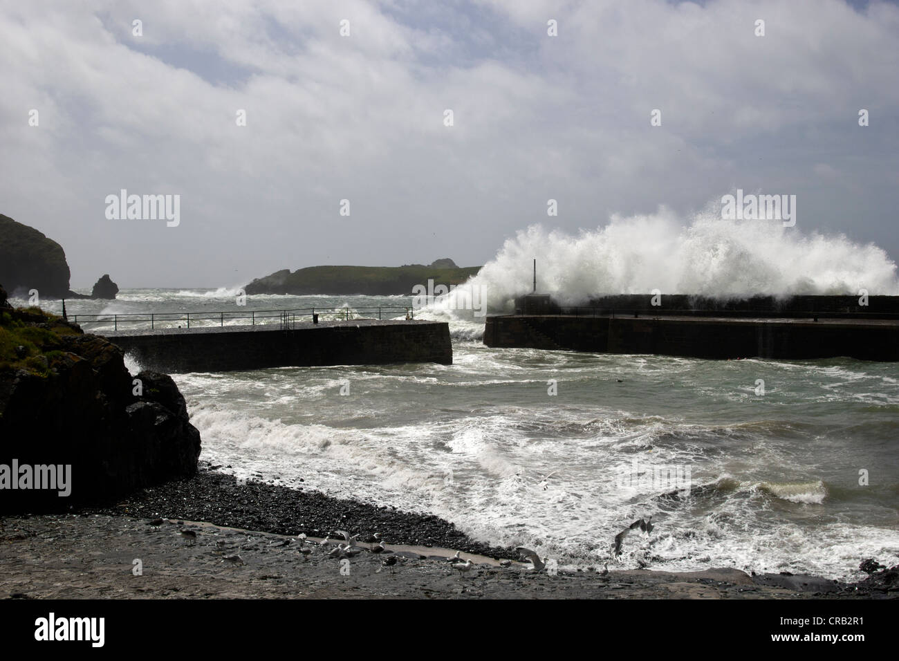 Crashing waves at Mullion Cove, The Lizard, Cornwall cause by a south westerly gale force wind. - Stock Image