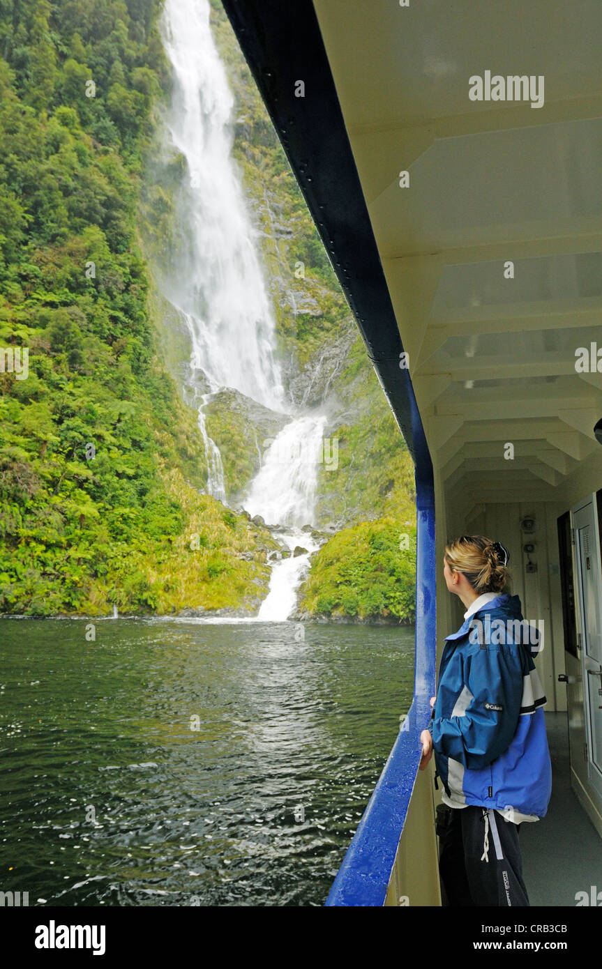 Woman leaning against the railing of the ship Fiordland Navigator, a waterfall at the back, Doubtful Sound cruise, - Stock Image
