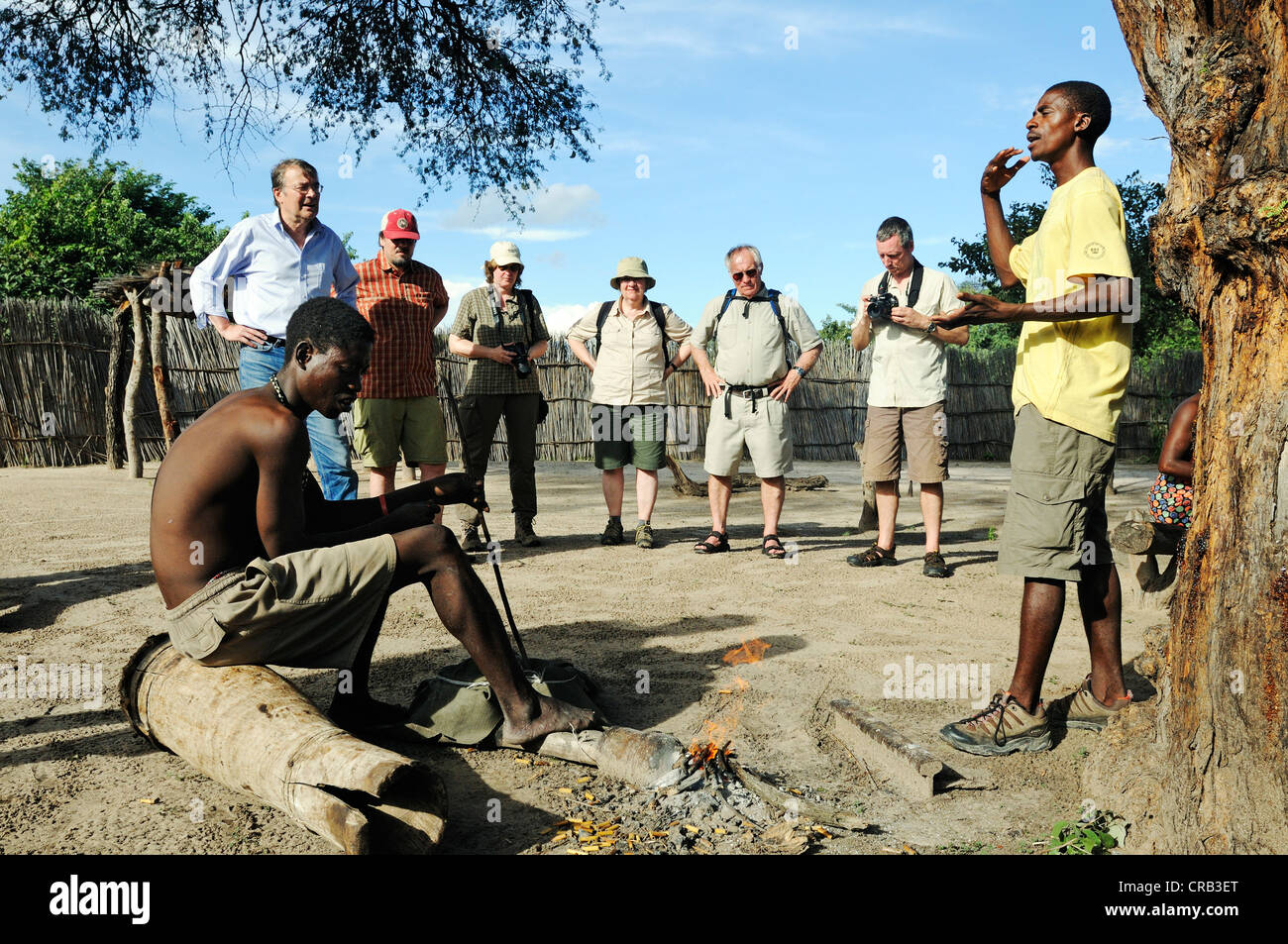 Tour guide and tourists on a guided tour of a traditional village near Camp Kwando on the Kwando River - Stock Image