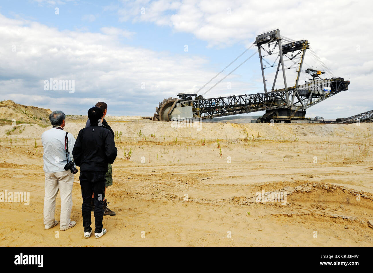 Tourists in front of a Bucket-wheel excavator in the open pit Welzow-Sued, mining of brown coal by the Vattenfall Stock Photo