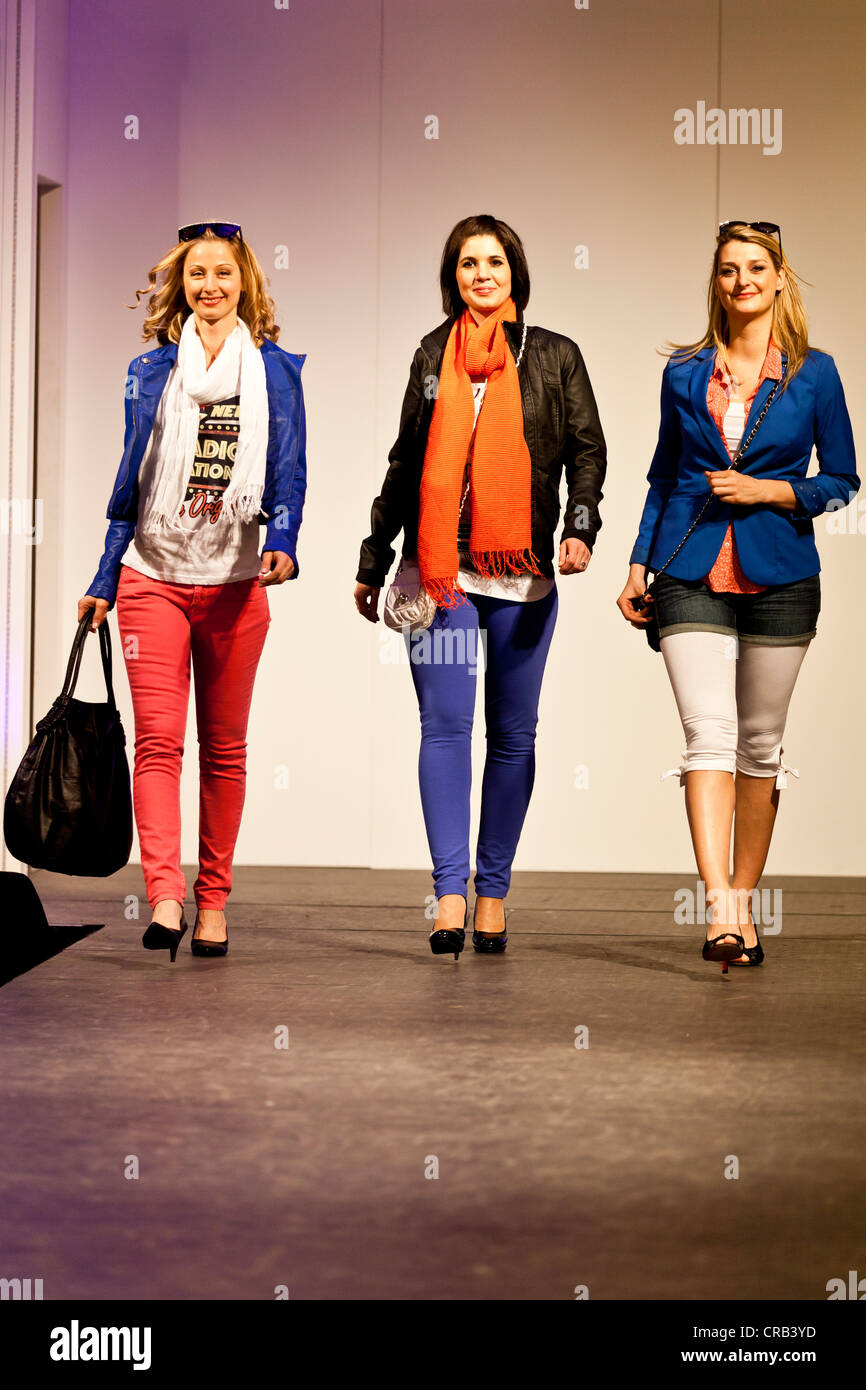 Three female models on the catwalk at a 2012 spring fashion show in Emmen, Lucerne, Switzerland, Europe - Stock Image