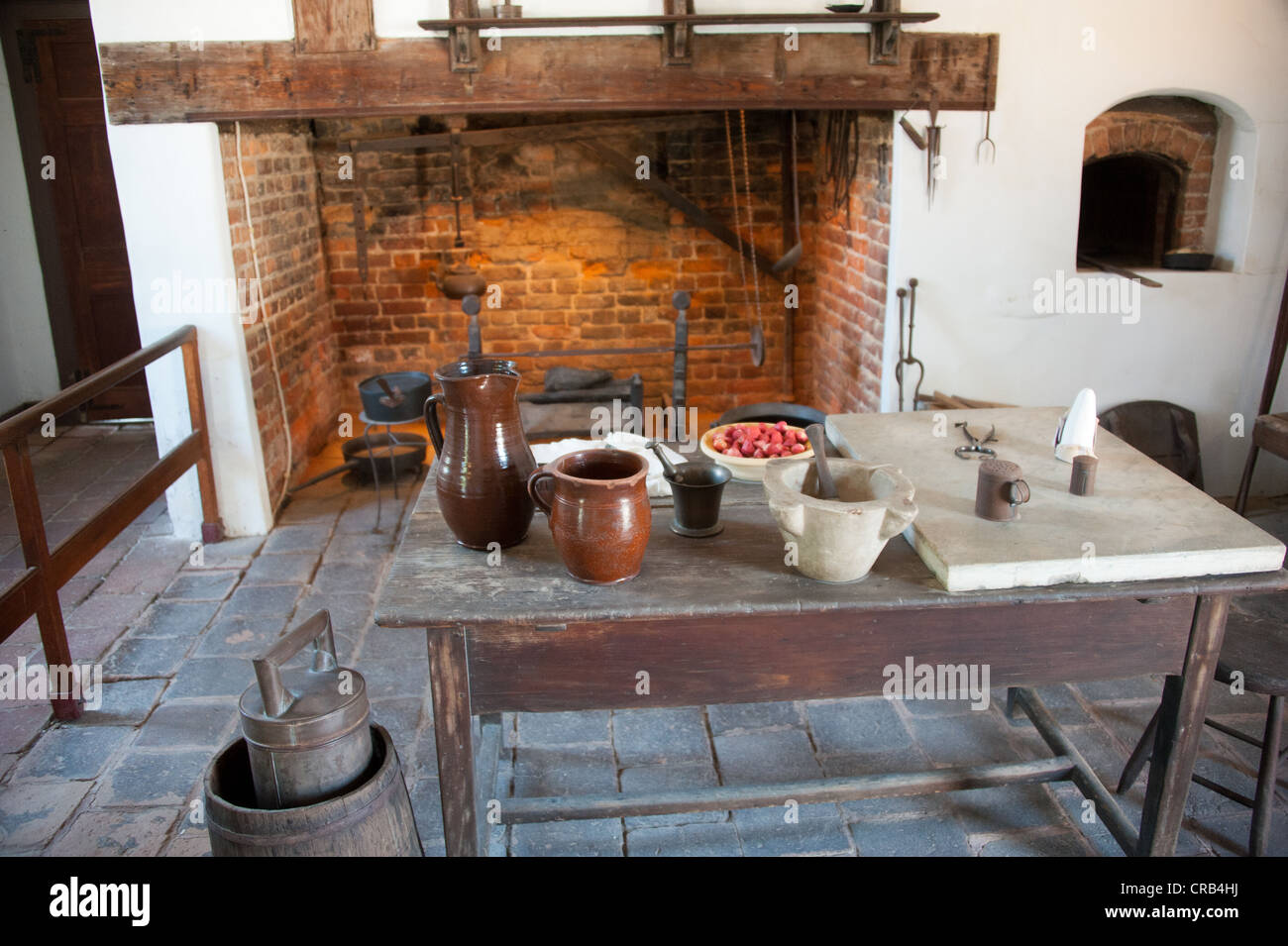 Pioneer style kitchen with brick oven and table with jars and pots Stock Photo