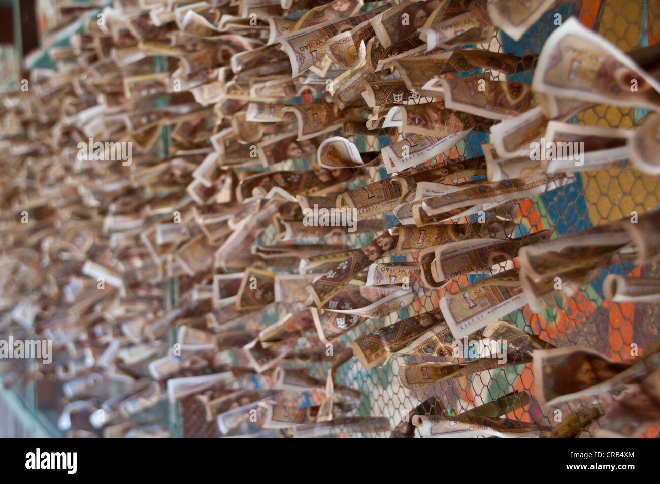Money donated by pilgrims on a fence in Gyantse, Tibet, Asia - Stock Image