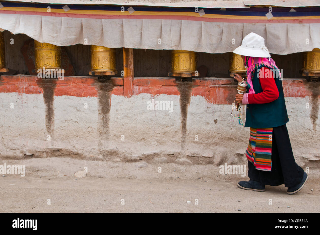 Old woman turning prayer wheels, kingdom of Guge, Western Tibet, Tibet, Asia - Stock Image