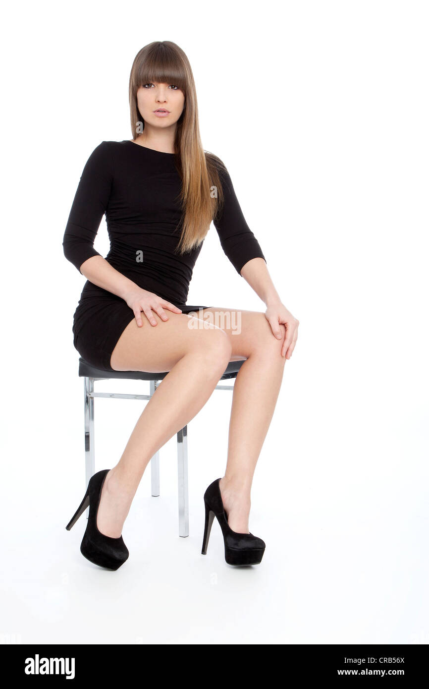 95da164fcb85 Young woman posing confidently in a short black dress with high heels