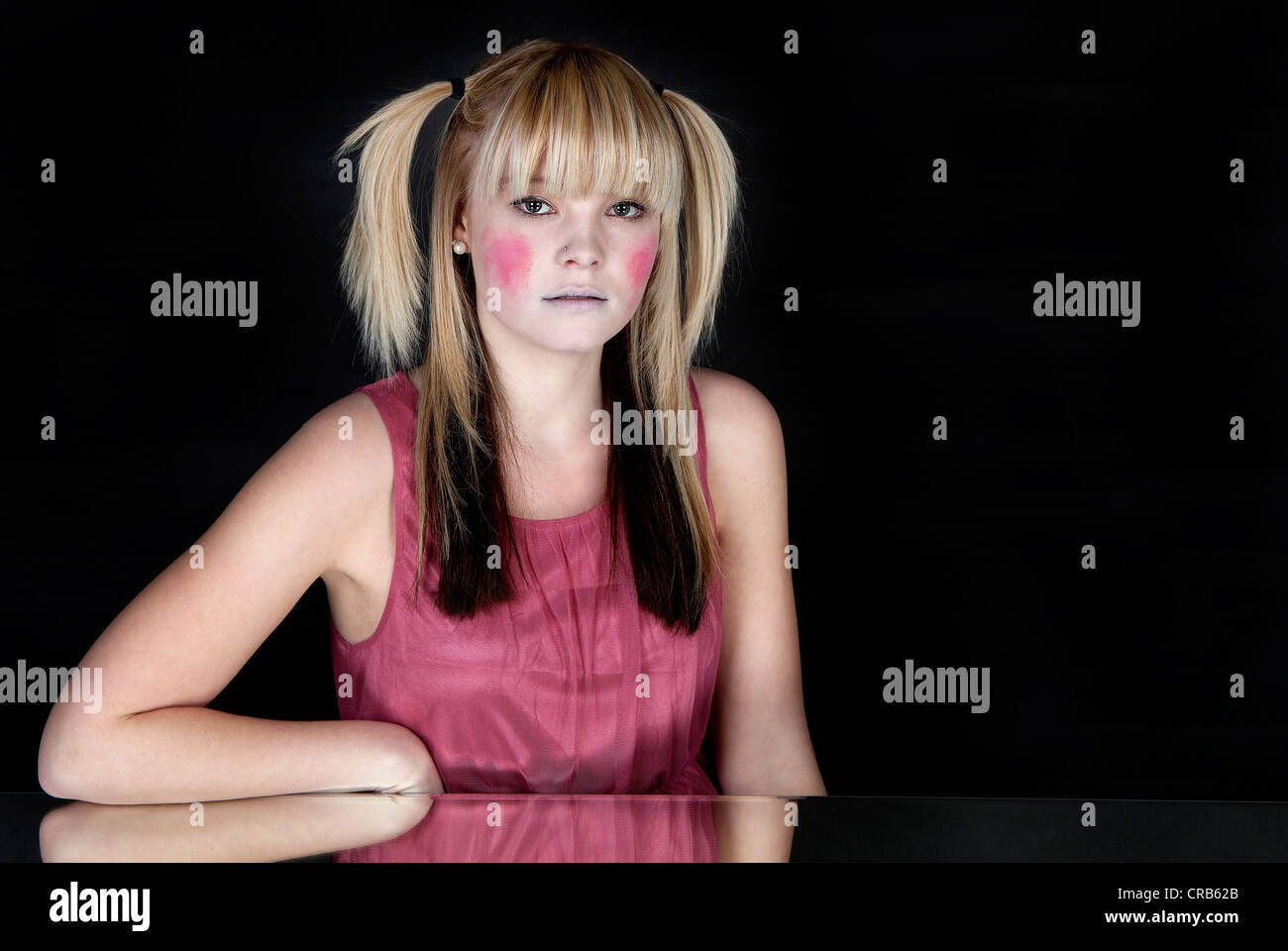 Young blond woman with red painted cheeks - Stock Image