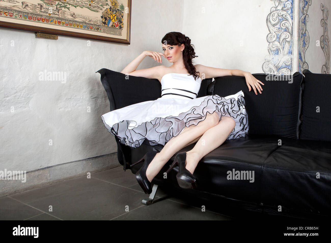 Young woman wearing a white dress sitting on a sofa - Stock Image