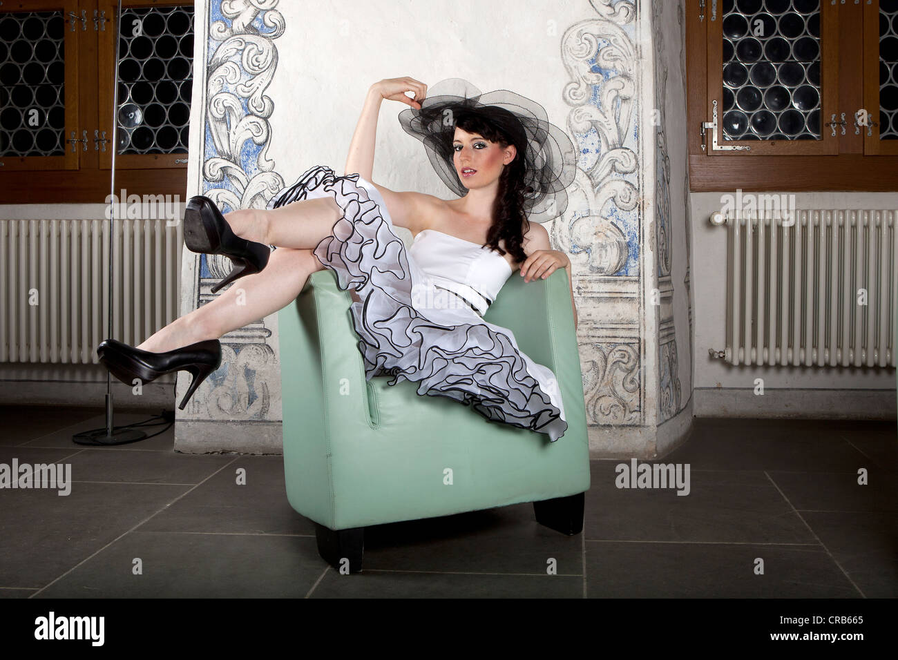 Young woman wearing a headdress and a white dress, posing on a chair - Stock Image