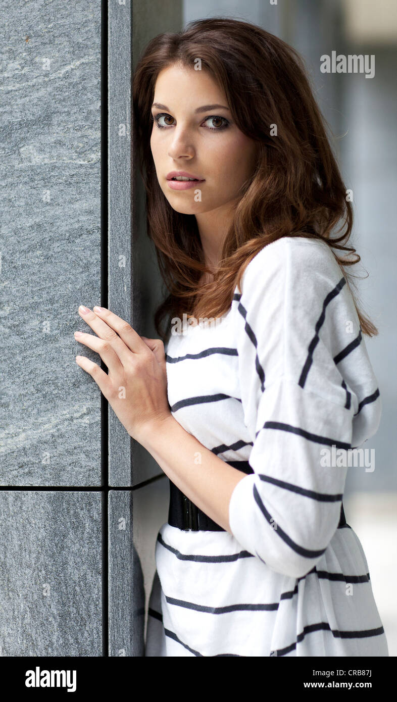 Young woman wearing a black and white striped dress leaning against a grey wall - Stock Image