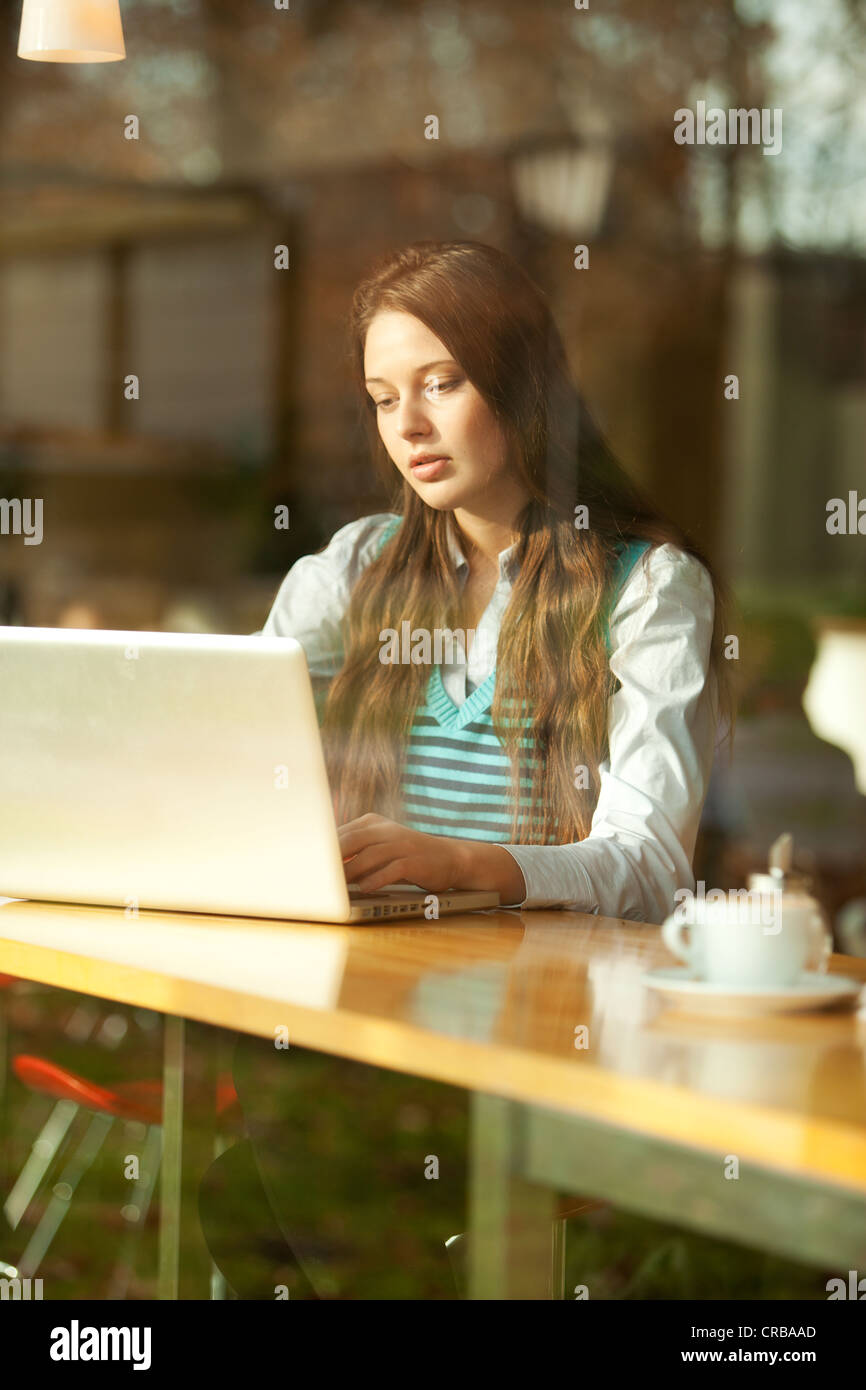 Student with a laptop sitting in a cafe, seen through a window - Stock Image
