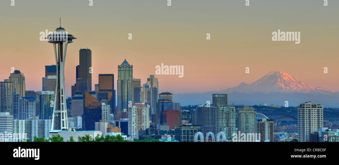 Skyline at dusk, Seattle financial district with Space Needle, Mount Rainier at back, Columbia Center - Stock Image