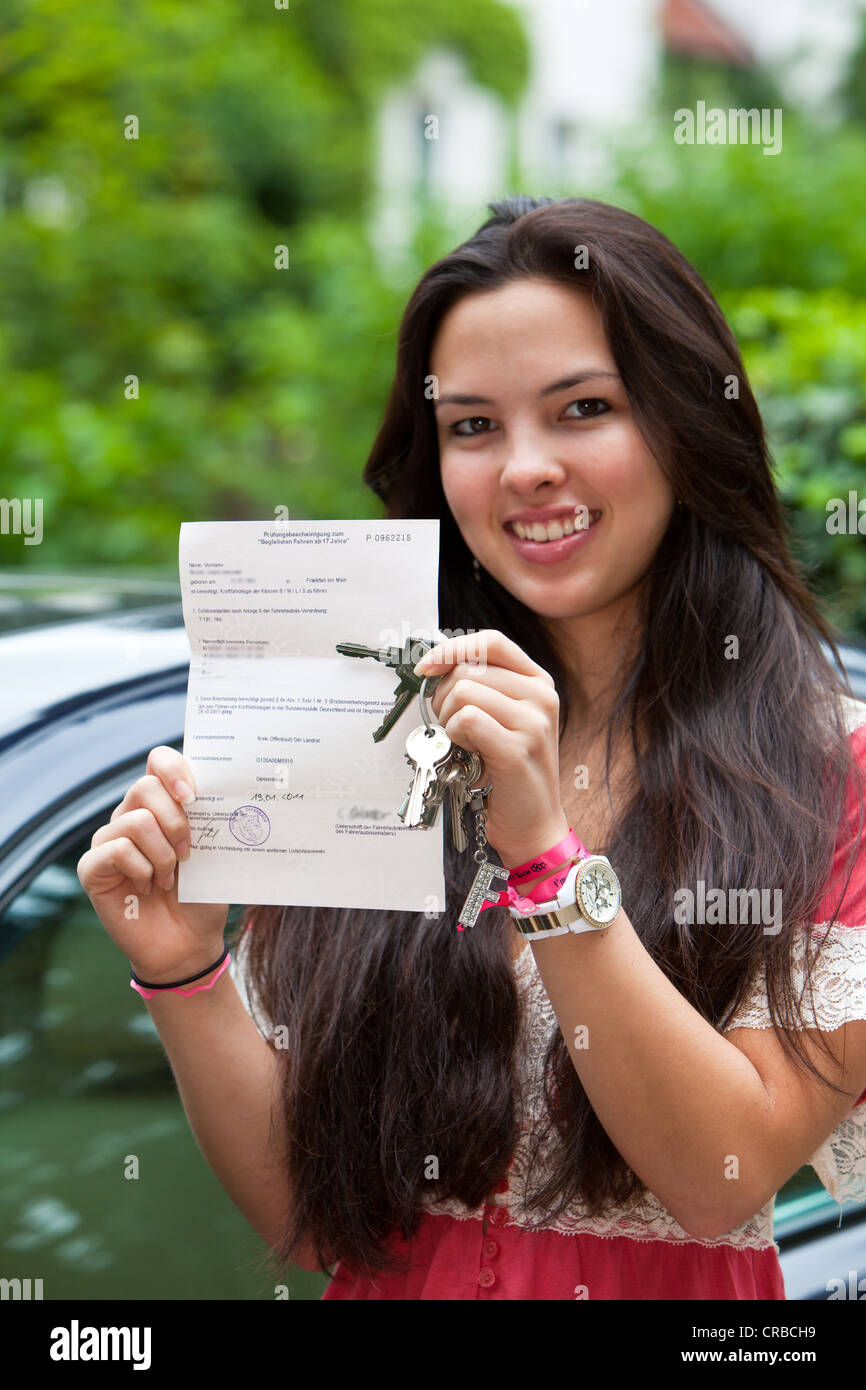Girl, about 17 years, proudly presenting her driving license for 'Accompanied Driving for Drivers Aged 17+', - Stock Image