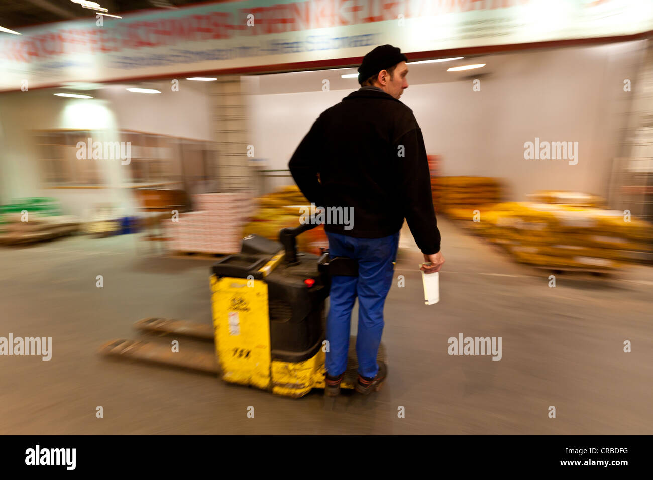 Workers drives hand lift with goods in a wholesale for fresh produce, fruits and vegetables, Frankfurt, Hesse, Germany, - Stock Image