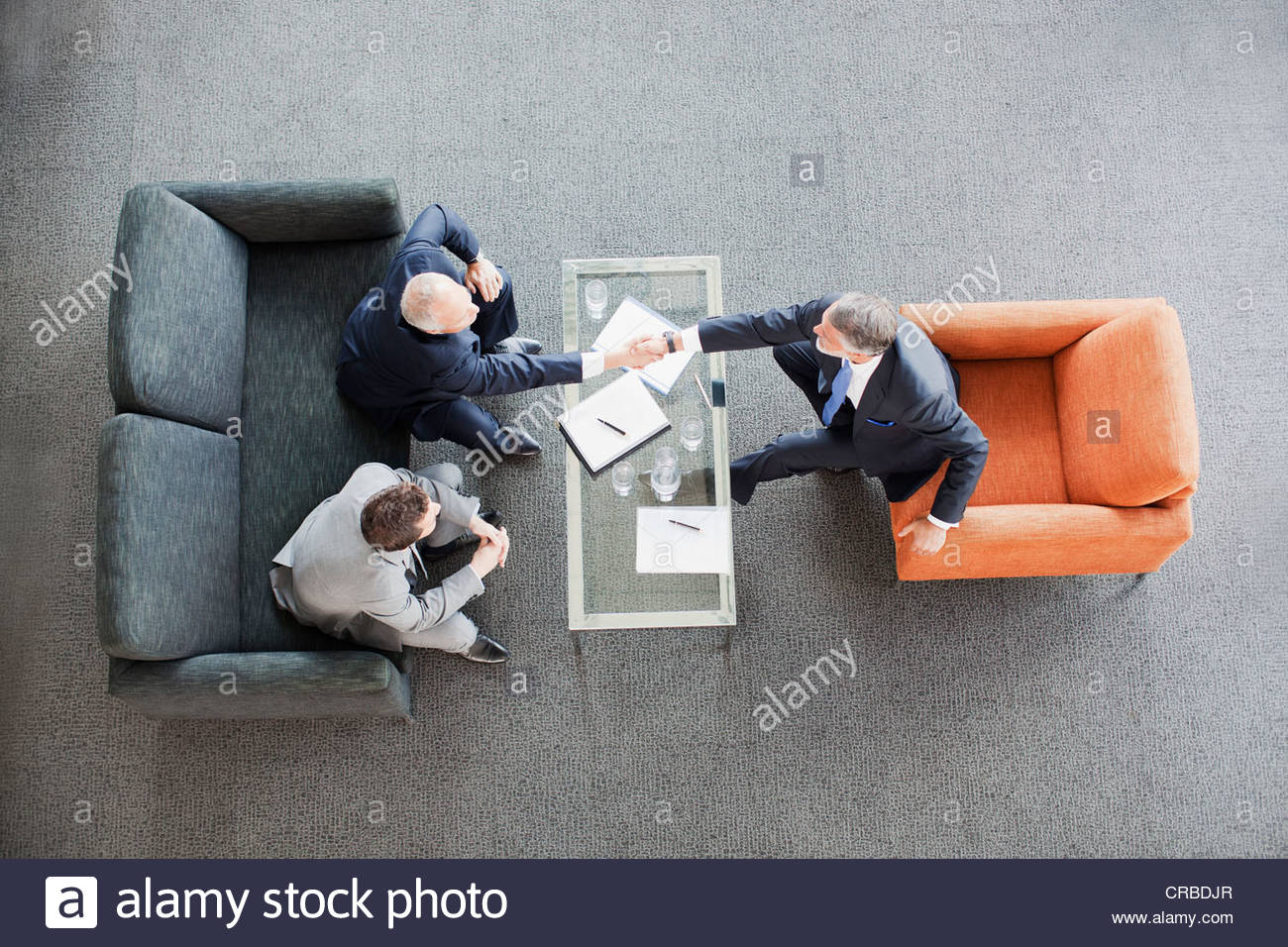 Businessmen shaking hands across coffee table in office lobby - Stock Image