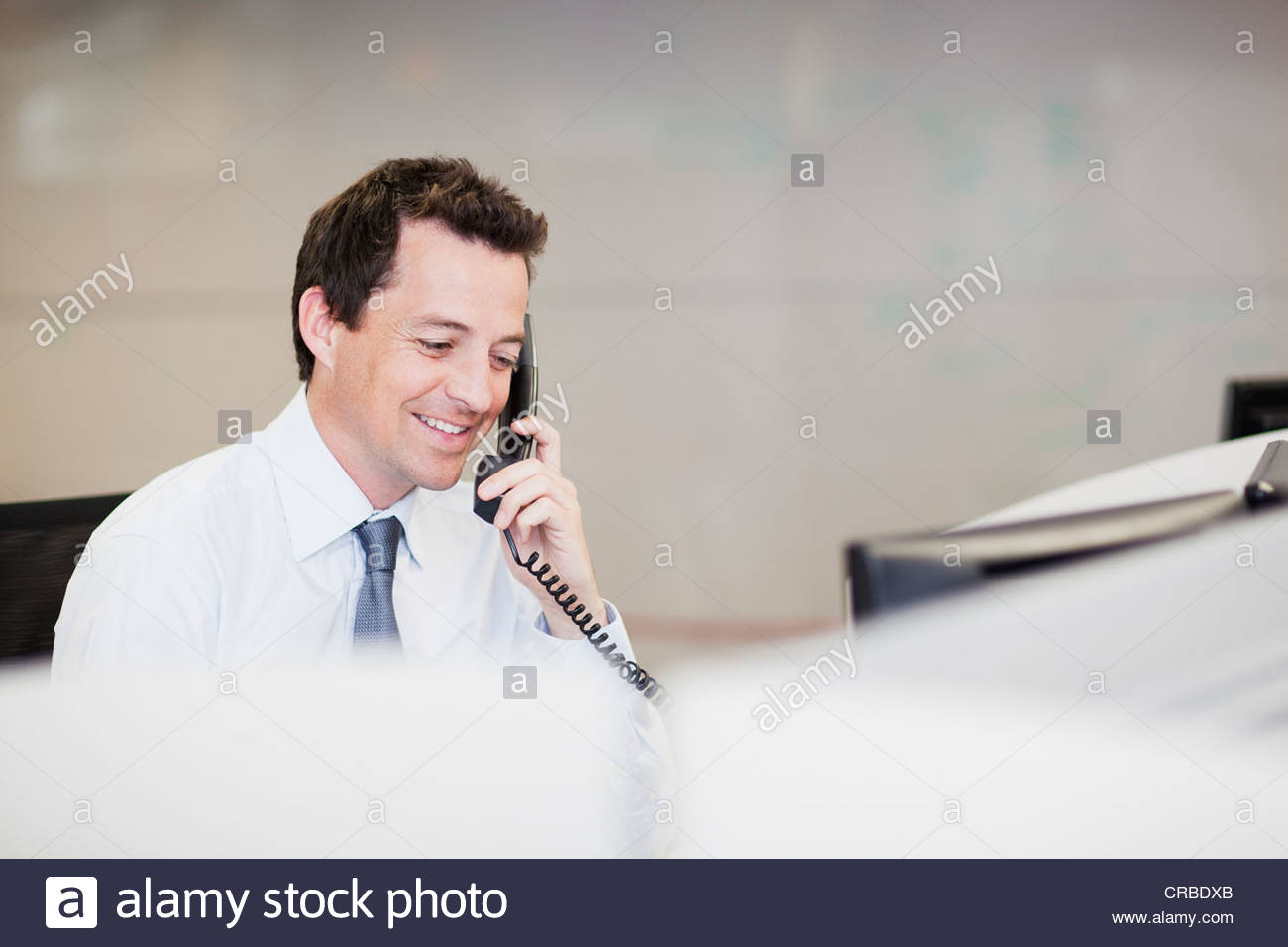 Smiling businessman talking on telephone in office - Stock Image
