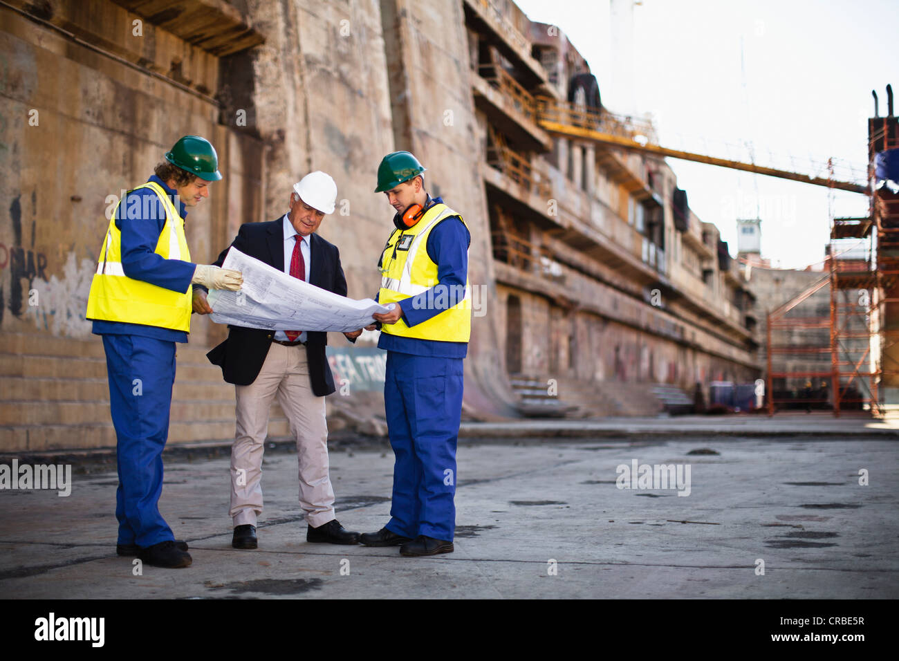 Workers reading blueprints on dry dock Stock Photo
