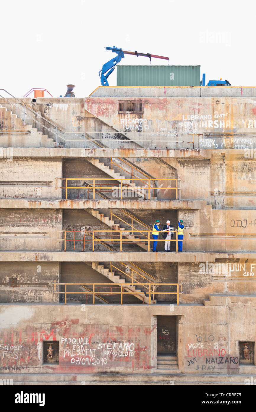 Workers talking on steps on dry dock - Stock Image