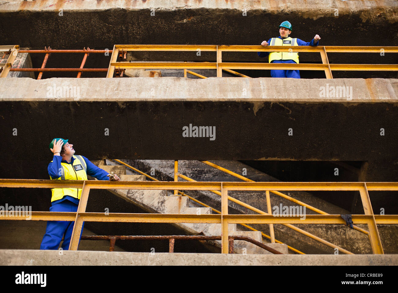 Workers shouting from different floors - Stock Image