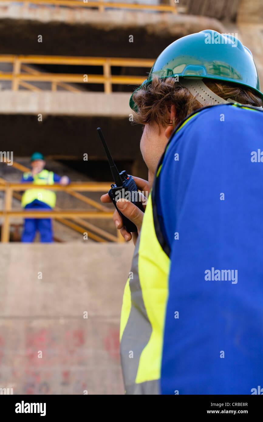Workers using walkie talkies on dry dock - Stock Image