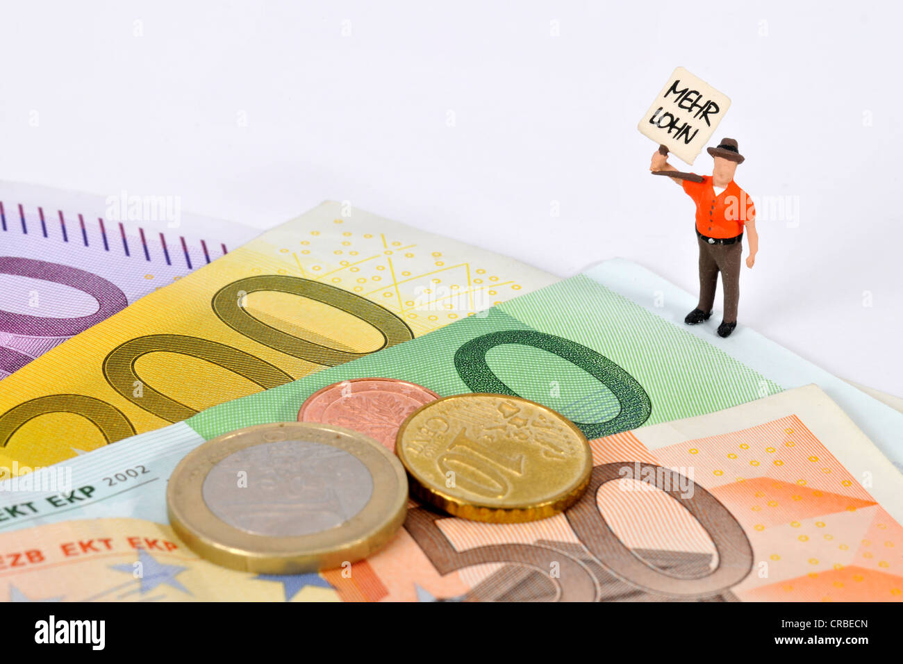 Miniature figurine holding a sign, Mehr Lohn, German for More Pay, beside euro banknotes and coins - Stock Image