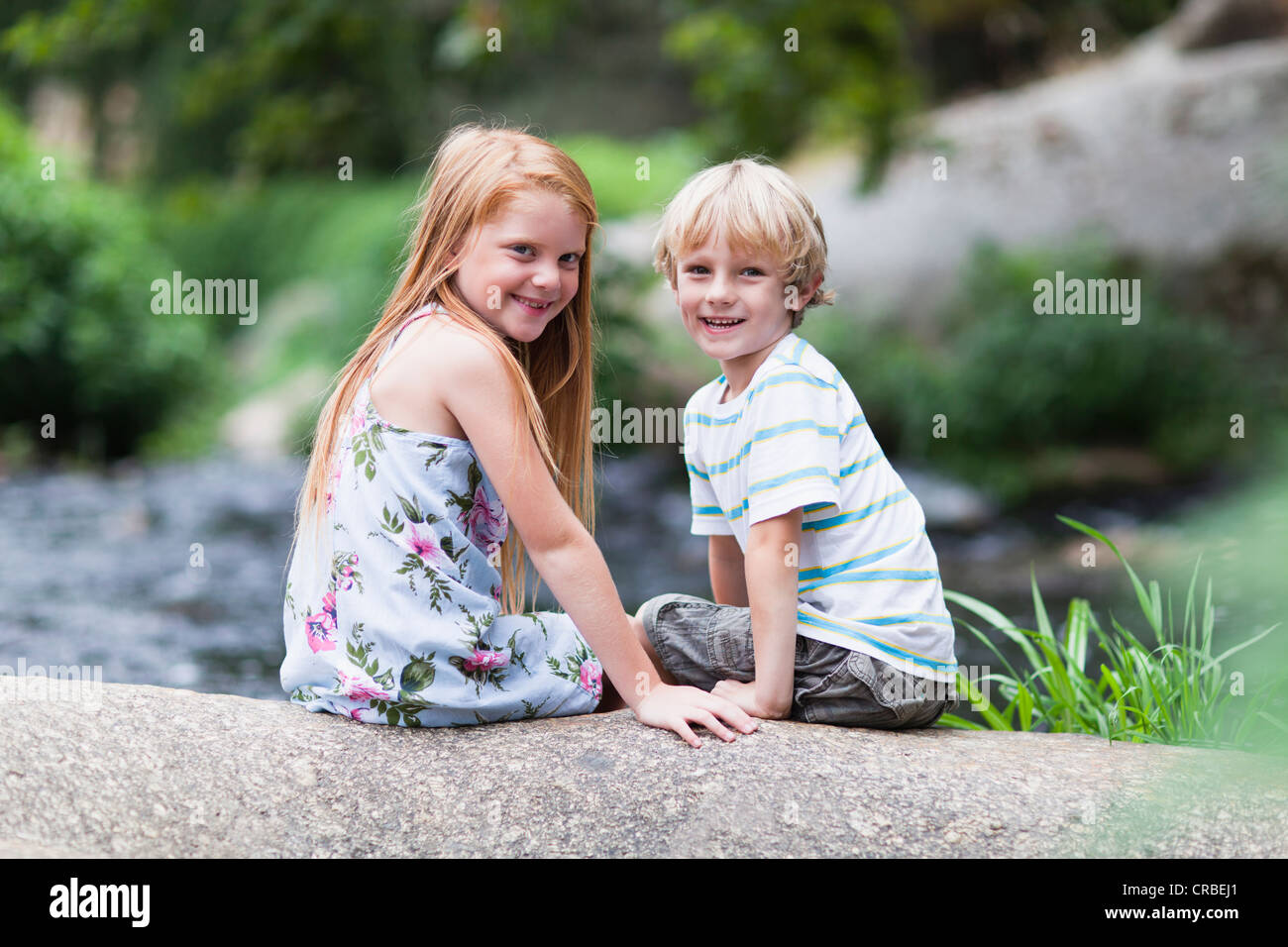 Children sitting on rock together - Stock Image