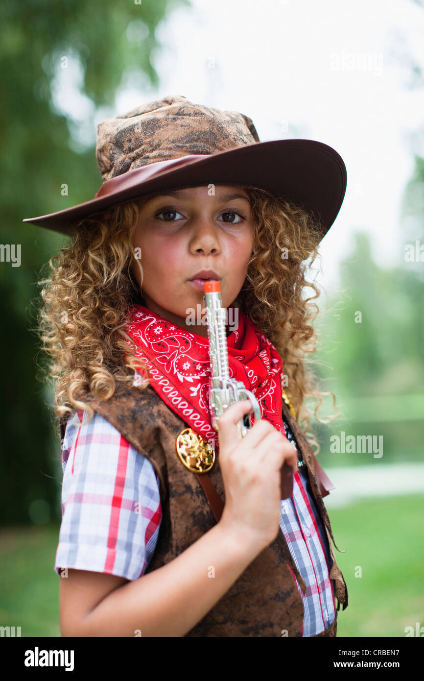 Girl in cowboy hat with toy pistol - Stock Image