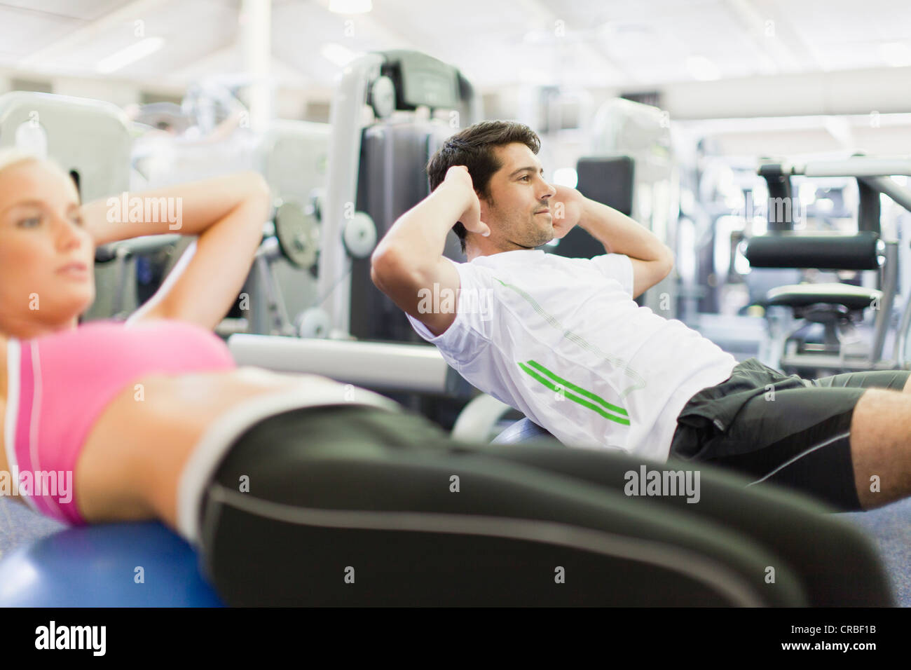 Couple working out together in gym - Stock Image