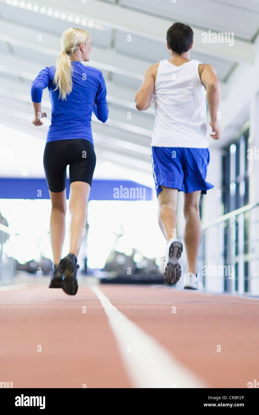Couple running on indoor track in gym - Stock Image