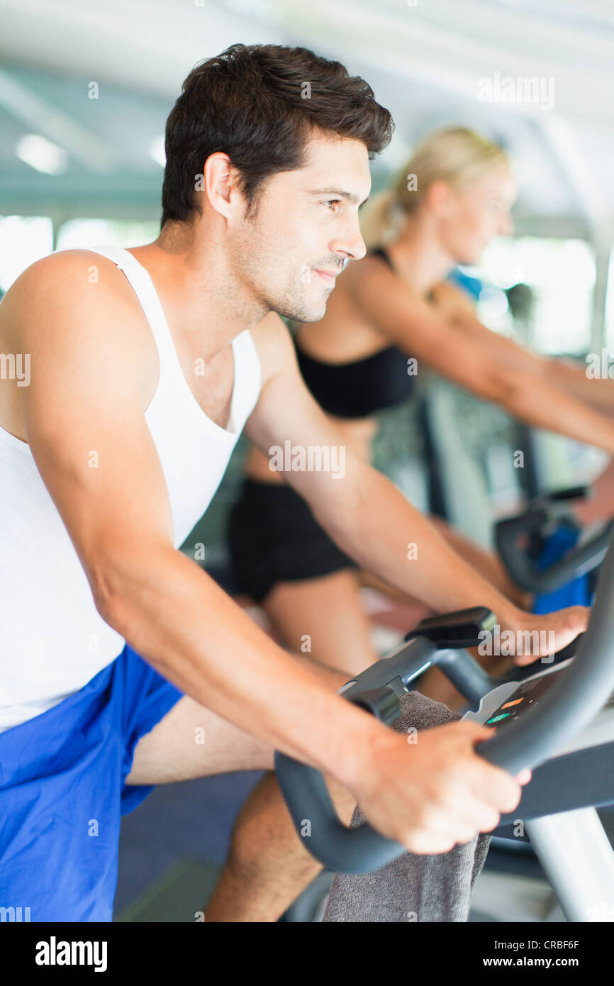 Couple using exercise machines in gym - Stock Image