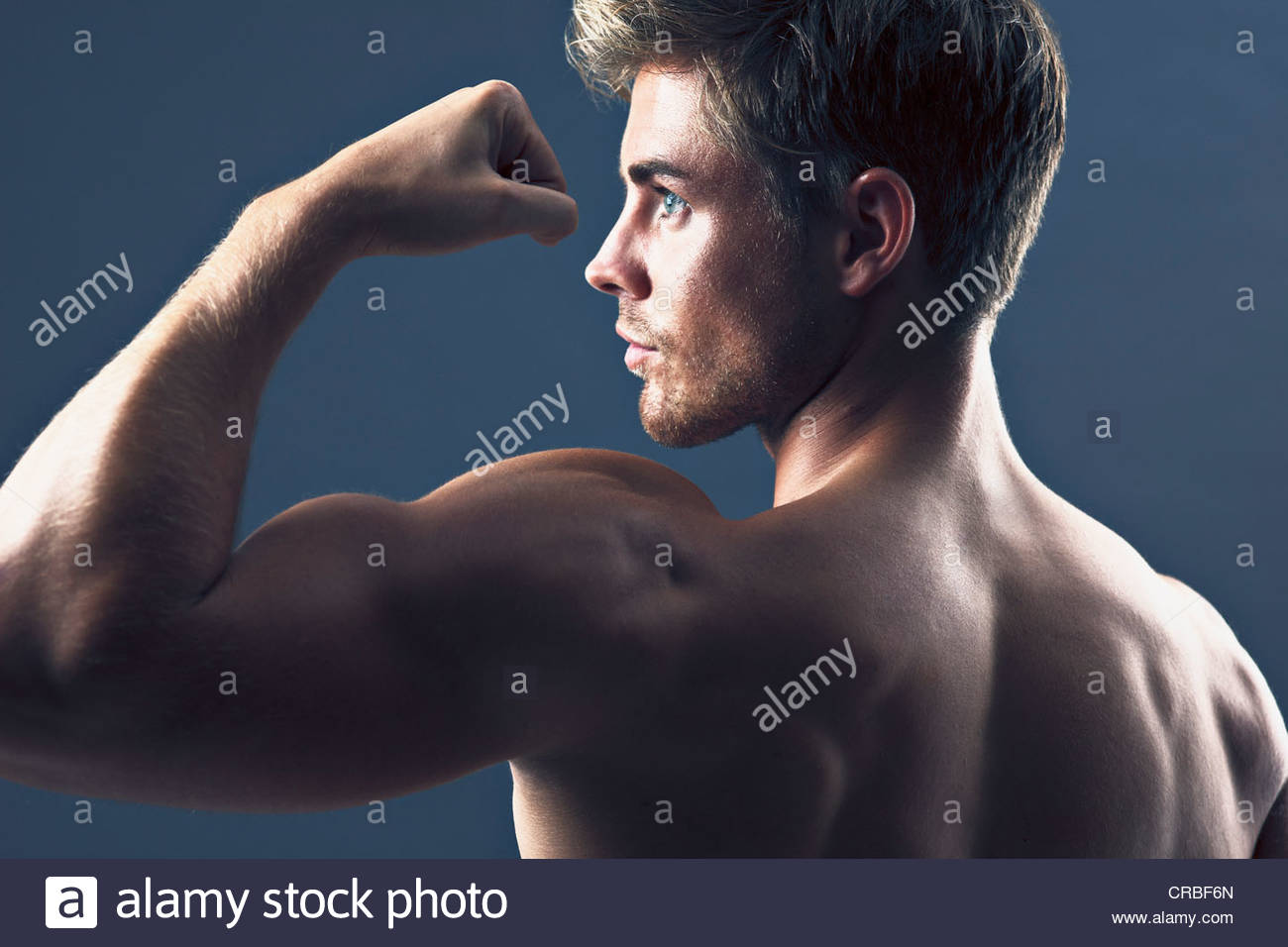 Rear view portrait of man flexing biceps muscles - Stock Image