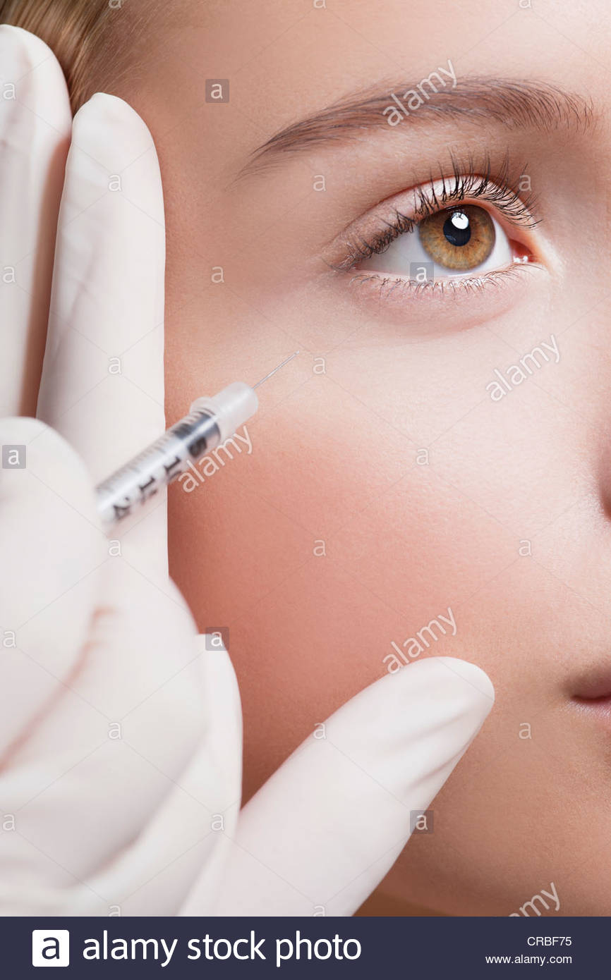 Close up of woman receiving botox injection under eye Stock