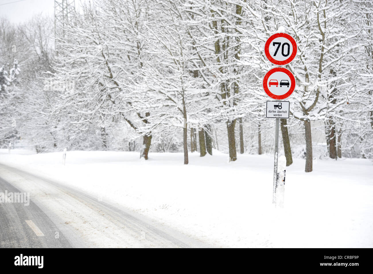 Snow-covered country road in winter, mandatory-sign, prohibition sign - Stock Image