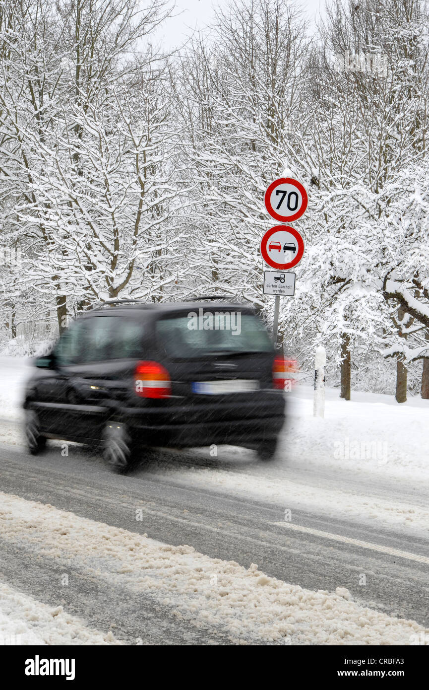 Snow-covered country road in winter, mandatory-sign, prohibition sign, car, motion blur - Stock Image