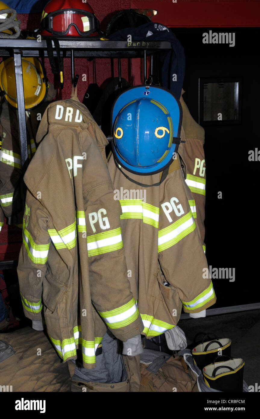 firefighters turnout gear hanging on a wall in a firehouse in Bladensburg, Maryland - Stock Image