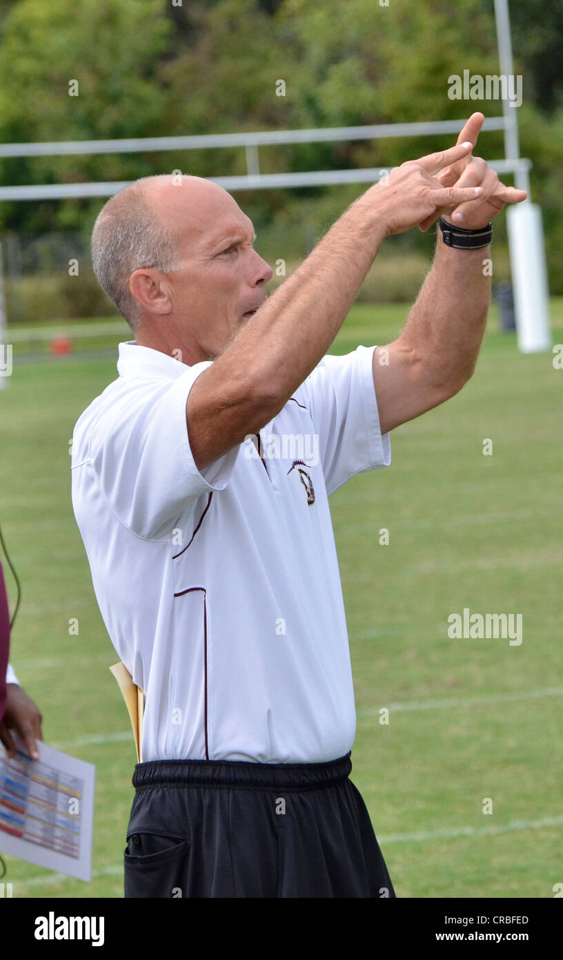Coach gestures plays from the sidelines at a high school football game in Maryland Stock Photo